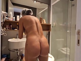Brazilian dark haired with large, permanent hooters, Bianca Naldy is getting banged from the back, in the shower